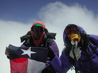 Against a bright blue sky with a wispy cloud, two people hold up a Texas flag. They are both heavily clothed with goggles obscuring their faces, and one also wears what appears to be an oxygen mask.