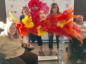 In front of a ZACH theater step and repeat banner, a space for photos has been set up with a cut-out of a pink-haired drag queen's smiling face surrounded by orange, red, and yellow feathers and flowers. Two women sitting in wheelchairs are in front of the display and two other women stand behind it, one sticking her tongue out.