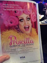 A hand holds open a program booklet to a page where a made up drag queen with a pink curly headpiece and orange feather boa opens her mouth in a big smile toward the viewer. The words Priscilla Queen of the Desert appear at the bottom of the page.