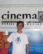 William raises his mug in a toast in front on the Cinema Touching Disability banner