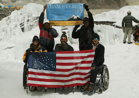 On a bright, snowy field, three warmly clothed men sitting in wheelchairs hold up a flag, which resembles the American with the field of stars replaced by a figure in a wheelchair. Behind them, two more bundled up people stand, holding up a smaller banner that reads Team Everest 03