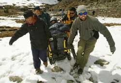 Over snow, four bundled up men carry a fifth in a wheelchair, each taking a corner of the chair.