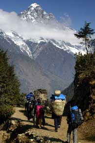 With a snow-capped mountain and clouds in the background, a large group of people with towering packs on their backs walk up a dirt trail.