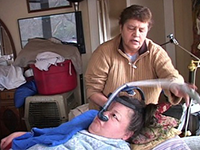 A woman in a bed looks at a breathing tube on her face, while another woman behind the bed adjusts it.