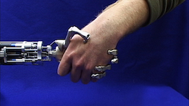 Against a deep blue background, a spindly robotic hand grips a human hand.