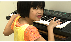 A girl playing the keyboard looks over her shoulder and smiles toward the camera