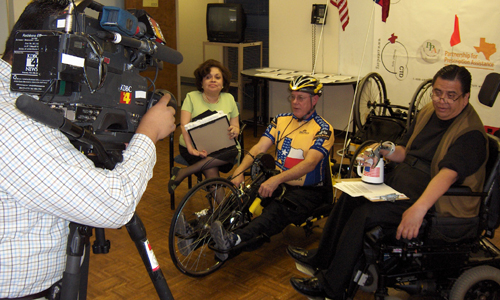 Seated woman, male hand-cyclist, and man sitting in wheelchair face a TV camera