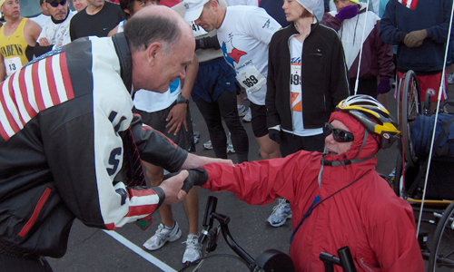 A man bends down to shake hands with hand-cyclist
