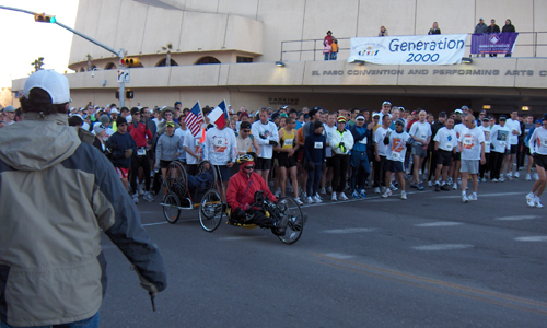 A crowd of people stand behind hand-cyclist